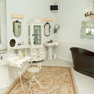 Inspiration for a large shabby-chic style master bathroom in Charlotte with a freestanding tub, a pedestal sink, furniture-like cabinets, white cabinets, white tile, ceramic tile, blue walls and porcelain floors.