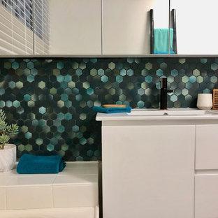 Ejemplo de cuarto de baño vintage con bañera encastrada, baldosas y/o azulejos verdes, baldosas y/o azulejos de cerámica, paredes blancas, suelo de azulejos de cemento, encimera de azulejos, suelo turquesa y encimeras blancas