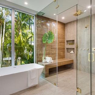 Foto di una stanza da bagno minimal con vasca freestanding, doccia a filo pavimento, piastrelle grigie, pareti grigie, pavimento in cemento, pavimento grigio, porta doccia a battente, nicchia e panca da doccia