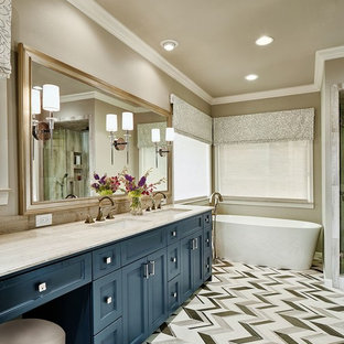 Diseño de cuarto de baño principal, clásico renovado, de tamaño medio, con armarios con paneles empotrados, puertas de armario azules, bañera exenta, paredes beige, lavabo bajoencimera, sanitario de dos piezas, baldosas y/o azulejos blancas y negros, baldosas y/o azulejos grises, baldosas y/o azulejos en mosaico, suelo de linóleo, encimera de granito y encimeras beige