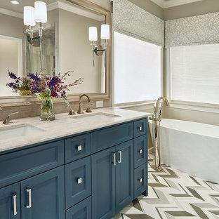 ダラスの中くらいのトランジショナルスタイルのおしゃれなマスターバスルーム (落し込みパネル扉のキャビネット、青いキャビネット、置き型浴槽、ベージュの壁、アンダーカウンター洗面器、分離型トイレ、リノリウムの床、御影石の洗面台) の写真