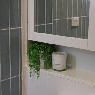 Esempio di una piccola stanza da bagno con doccia moderna con ante bianche, WC monopezzo, piastrelle blu, piastrelle in gres porcellanato, pavimento alla veneziana, top in superficie solida e top grigio