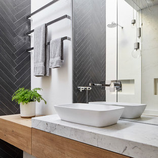 This is an example of a contemporary bathroom in Melbourne with flat-panel cabinets, light wood cabinets, gray tile, white walls, a vessel sink and grey floor.
