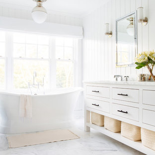 Freestanding bathtub - mid-sized beach style master white floor and marble floor freestanding bathtub idea in New York with furniture-like cabinets, white cabinets, white walls, an undermount sink, white countertops, a one-piece toilet and marble countertops