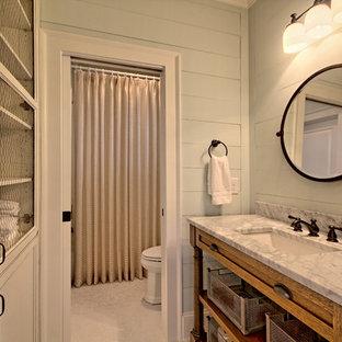 Foto de cuarto de baño con ducha, de estilo de casa de campo, de tamaño medio, con armarios con paneles empotrados, puertas de armario con efecto envejecido, combinación de ducha y bañera, sanitario de dos piezas, paredes grises, suelo con mosaicos de baldosas y encimera de mármol