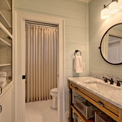 Inspiration for a mid-sized country 3/4 mosaic tile floor tub/shower combo remodel in Atlanta with recessed-panel cabinets, distressed cabinets, a two-piece toilet, gray walls and marble countertops