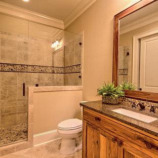 Modelo de cuarto de baño con ducha, rústico, pequeño, con armarios con paneles empotrados, puertas de armario de madera clara, ducha empotrada, sanitario de dos piezas, baldosas y/o azulejos multicolor, baldosas y/o azulejos en mosaico, paredes beige, suelo de travertino, lavabo bajoencimera y encimera de granito