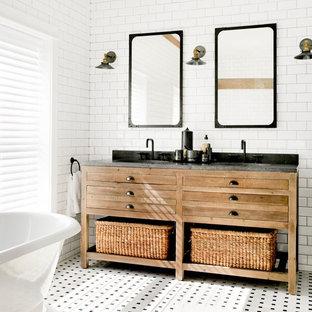 Diseño de cuarto de baño principal, campestre, grande, con armarios tipo mueble, puertas de armario marrones, bañera exenta, baldosas y/o azulejos blancos, baldosas y/o azulejos de cerámica, suelo con mosaicos de baldosas, encimera de granito y suelo blanco