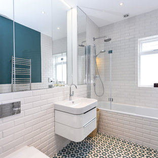 Design ideas for a medium sized contemporary ensuite bathroom in London with flat-panel cabinets, white cabinets, a built-in bath, a shower/bath combination, metro tiles, blue walls, ceramic flooring, a wall-mounted sink, multi-coloured floors, a hinged door and white tiles.