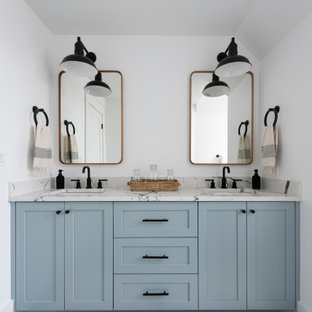 Свежая идея для дизайна: большая детская ванная комната в стиле кантри с плоскими фасадами, синими фасадами, ванной в нише, раздельным унитазом, белой плиткой, керамогранитной плиткой, белыми стенами, полом из сланца, врезной раковиной, столешницей из искусственного кварца, черным полом, белой столешницей, нишей, тумбой под две раковины, встроенной тумбой и сводчатым потолком - отличное фото интерьера