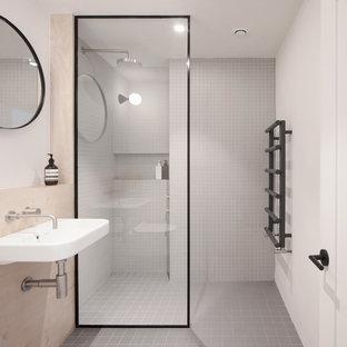 Immagine di una piccola stanza da bagno con doccia scandinava con zona vasca/doccia separata, piastrelle grigie, piastrelle a listelli, pareti bianche, lavabo sospeso, pavimento grigio e doccia aperta