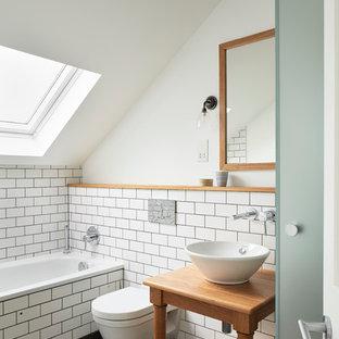 Modelo de cuarto de baño principal, contemporáneo, pequeño, con armarios abiertos, puertas de armario de madera oscura, bañera encastrada, sanitario de pared, paredes blancas, suelo de pizarra, encimera de madera, lavabo sobreencimera y encimeras marrones