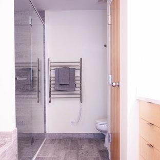 Foto på ett litet funkis grå en-suite badrum, med släta luckor, skåp i ljust trä, ett platsbyggt badkar, våtrum, en toalettstol med hel cisternkåpa, grå kakel, keramikplattor, vita väggar, klinkergolv i keramik, ett undermonterad handfat, bänkskiva i kvarts, grått golv och dusch med gångjärnsdörr