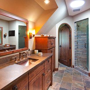 Esempio di una grande stanza da bagno padronale country con lavabo sottopiano, ante in legno scuro, ante con riquadro incassato, piastrelle in ardesia e top marrone