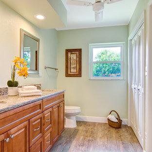 Ejemplo de cuarto de baño principal, retro, con armarios con paneles empotrados, puertas de armario naranjas, sanitario de dos piezas, suelo de madera clara, lavabo bajoencimera, encimera de granito y suelo beige