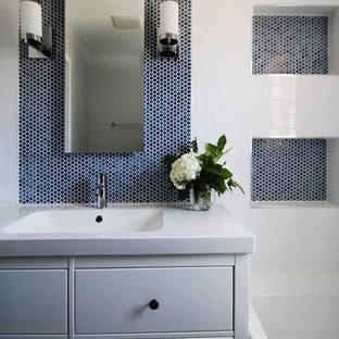 Foto de cuarto de baño moderno, pequeño, con armarios con paneles lisos, puertas de armario blancas, bañera empotrada, combinación de ducha y bañera, sanitario de una pieza, baldosas y/o azulejos blancos, baldosas y/o azulejos de porcelana, paredes azules, suelo de baldosas de porcelana, lavabo integrado y encimera de cuarzo compacto