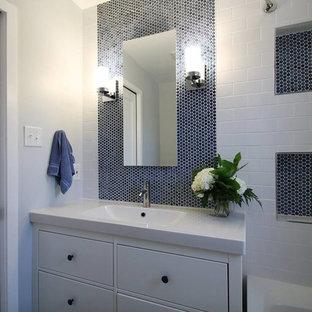 Diseño de cuarto de baño minimalista, pequeño, con armarios con paneles lisos, puertas de armario blancas, bañera empotrada, combinación de ducha y bañera, sanitario de una pieza, baldosas y/o azulejos blancos, baldosas y/o azulejos de porcelana, paredes azules, suelo de baldosas de porcelana, lavabo integrado y encimera de cuarzo compacto