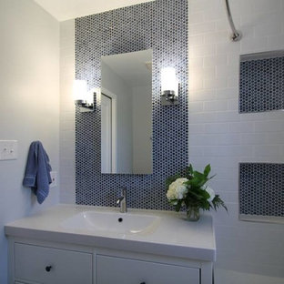 Small minimalist white tile and porcelain tile porcelain floor bathroom photo in Denver with flat-panel cabinets, white cabinets, a one-piece toilet, blue walls, an integrated sink and quartz countertops