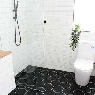 Idéer för att renovera ett litet funkis beige beige badrum för barn, med skåp i shakerstil, vita skåp, en öppen dusch, en toalettstol med hel cisternkåpa, vit kakel, keramikplattor, vita väggar, klinkergolv i porslin, ett fristående handfat, träbänkskiva, svart golv och med dusch som är öppen