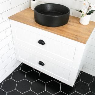 パースの小さいモダンスタイルのおしゃれな子供用バスルーム (シェーカースタイル扉のキャビネット、白いキャビネット、オープン型シャワー、一体型トイレ、白いタイル、セラミックタイル、白い壁、磁器タイルの床、ベッセル式洗面器、木製洗面台、黒い床、オープンシャワー、ベージュのカウンター、洗面台1つ、フローティング洗面台、レンガ壁) の写真