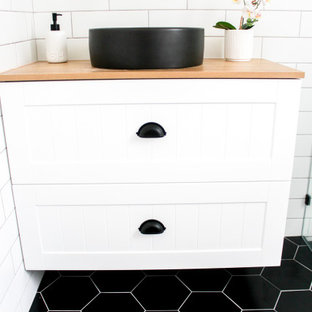 Small minimalist kids' white tile and ceramic tile porcelain tile, black floor, single-sink and brick wall bathroom photo in Perth with shaker cabinets, white cabinets, a one-piece toilet, white walls, a vessel sink, wood countertops, beige countertops and a floating vanity