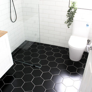 Photo of a small modern kids bathroom in Perth with shaker cabinets, white cabinets, an open shower, a one-piece toilet, white tile, ceramic tile, white walls, porcelain floors, a vessel sink, wood benchtops, black floor, an open shower, beige benchtops, a single vanity, a floating vanity and brick walls.