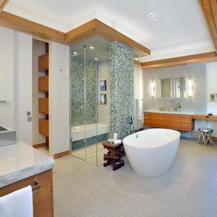 トロントの巨大なエクレクティックスタイルのおしゃれなマスターバスルーム (ベッセル式洗面器、フラットパネル扉のキャビネット、中間色木目調キャビネット、クオーツストーンの洗面台、置き型浴槽、バリアフリー、分離型トイレ、ベージュのタイル、磁器タイル、ベージュの壁、磁器タイルの床) の写真