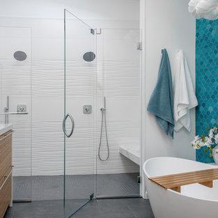 Idéer för ett modernt en-suite badrum, med släta luckor, skåp i mellenmörkt trä, ett fristående badkar, en kantlös dusch, blå kakel, vita väggar, ett undermonterad handfat, grått golv och dusch med gångjärnsdörr