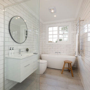Klassisches Kinderbad mit gelben Schränken, freistehender Badewanne, Eckdusche, weißen Fliesen, Keramikfliesen, weißer Wandfarbe, Unterbauwaschbecken, grauem Boden, Falttür-Duschabtrennung, weißer Waschtischplatte, Einzelwaschbecken und schwebendem Waschtisch in Melbourne