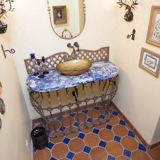 Modelo de cuarto de baño con ducha, de estilo americano, grande, con armarios con paneles con relieve, puertas de armario de madera oscura, ducha abierta, sanitario de una pieza, baldosas y/o azulejos de terracota, paredes beige, suelo de baldosas de terracota, lavabo sobreencimera, encimera de granito, suelo naranja y ducha con puerta corredera