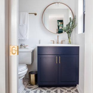 Diseño de cuarto de baño principal, escandinavo, pequeño, con armarios estilo shaker, puertas de armario azules, bañera empotrada, combinación de ducha y bañera, sanitario de dos piezas, paredes blancas, suelo de azulejos de cemento, lavabo bajoencimera, encimera de cuarzo compacto, suelo multicolor y ducha con cortina