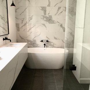 Стильный дизайн: большая главная ванная комната в современном стиле с плоскими фасадами, белыми фасадами, отдельно стоящей ванной, душем без бортиков, белой плиткой, мраморной плиткой, полом из сланца, врезной раковиной, мраморной столешницей, серым полом, душем с распашными дверями и белой столешницей - последний тренд