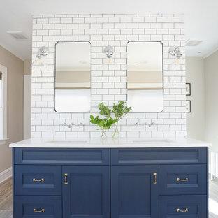 シカゴの中サイズのトランジショナルスタイルのおしゃれなマスターバスルーム (落し込みパネル扉のキャビネット、青いキャビネット、白いタイル、セラミックタイル、ベージュの壁、磁器タイルの床、アンダーカウンター洗面器、クオーツストーンの洗面台、ベージュの床、白い洗面カウンター) の写真