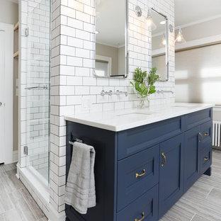 Cette image montre une douche en alcôve principale traditionnelle de taille moyenne avec un placard avec porte à panneau encastré, des portes de placard bleues, un carrelage blanc, des carreaux de céramique, un mur beige, un sol en carrelage de porcelaine, un lavabo encastré, un plan de toilette en quartz modifié, un plan de toilette blanc, un sol gris et une cabine de douche à porte battante.