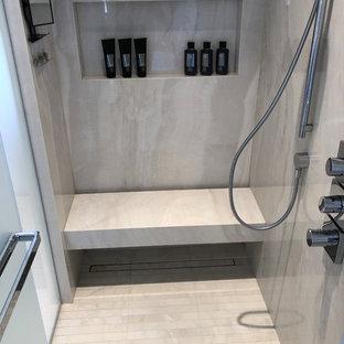 トロントの大きいコンテンポラリースタイルのおしゃれなマスターバスルーム (ベージュのタイル、磁器タイルの床、ベージュの床、開き戸のシャワー、シェーカースタイル扉のキャビネット、中間色木目調キャビネット、置き型浴槽、アルコーブ型シャワー、ライムストーンタイル、ベージュの壁、ベッセル式洗面器、ライムストーンの洗面台、ベージュのカウンター) の写真