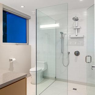 Immagine di una stanza da bagno design con ante lisce, vasca da incasso, doccia a filo pavimento, WC monopezzo, piastrelle bianche, lastra di pietra, pareti bianche, pavimento in pietra calcarea, lavabo sottopiano, top in superficie solida e ante arancioni