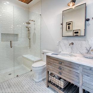 Lantlig inredning av ett badrum med dusch, med skåp i mellenmörkt trä, möbel-liknande, en kantlös dusch, vit kakel, vita väggar, ett undermonterad handfat, flerfärgat golv och dusch med gångjärnsdörr