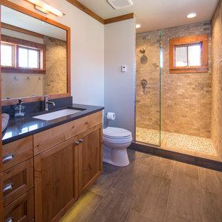 Foto de cuarto de baño principal, rústico, con lavabo bajoencimera, armarios estilo shaker, puertas de armario de madera oscura, encimera de cuarzo compacto, ducha abierta, baldosas y/o azulejos grises, baldosas y/o azulejos de porcelana, paredes blancas y suelo de baldosas de porcelana