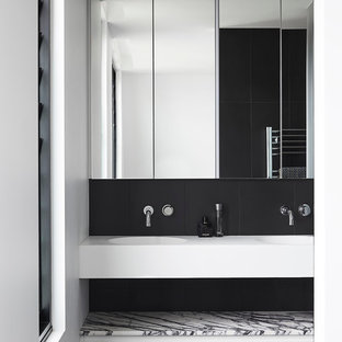 Photo of a medium sized contemporary ensuite bathroom in Melbourne with white cabinets, black tiles, porcelain tiles, white walls, porcelain flooring, marble worktops, flat-panel cabinets and an integrated sink.