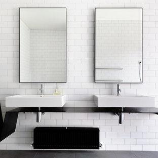 メルボルンの中サイズのコンテンポラリースタイルのおしゃれな浴室 (白いタイル、サブウェイタイル、黒いキャビネット、ドロップイン型浴槽、壁掛け式トイレ、白い壁、セラミックタイルの床、壁付け型シンク、ステンレスの洗面台) の写真