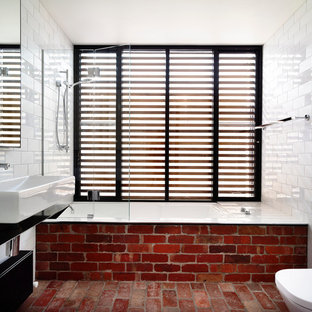 Mid-sized trendy white tile and subway tile brick floor and red floor bathroom photo in Melbourne with black cabinets, a wall-mount toilet, white walls, stainless steel countertops and a trough sink
