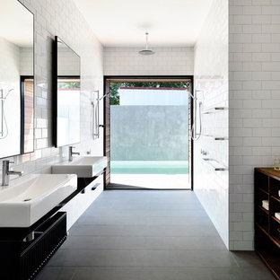 Новый формат декора квартиры: ванная комната среднего размера в современном стиле с подвесной раковиной, белой плиткой, плиткой кабанчик, открытыми фасадами, черными фасадами, белыми стенами, полом из керамической плитки, столешницей из нержавеющей стали, душем без бортиков и серым полом