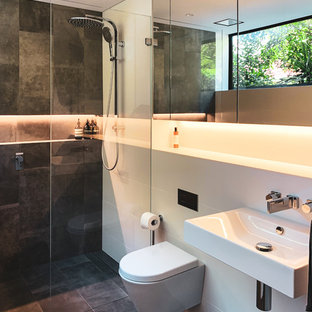 This is an example of a contemporary bathroom in Sydney with a curbless shower, a wall-mount toilet, gray tile, white tile, white walls, a wall-mount sink, grey floor and an open shower.