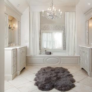 Imagen de cuarto de baño principal, clásico renovado, extra grande, con armarios tipo mueble, bañera empotrada, baldosas y/o azulejos grises, losas de piedra, suelo de piedra caliza, lavabo bajoencimera, encimera de piedra caliza, suelo beige, puertas de armario grises y paredes blancas