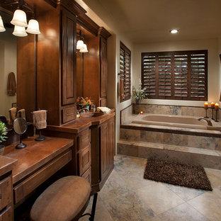 Ejemplo de cuarto de baño principal, rústico, de tamaño medio, con lavabo integrado, armarios tipo mueble, puertas de armario de madera oscura, encimera de granito, bañera empotrada, baldosas y/o azulejos beige, baldosas y/o azulejos de piedra, paredes beige y suelo de pizarra