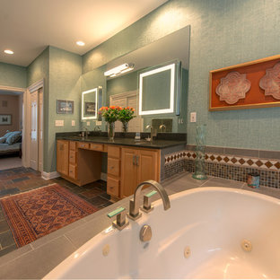 Large eclectic master beige tile, blue tile, brown tile, gray tile, multicolored tile and cement tile travertine floor alcove bathtub photo in Cincinnati with raised-panel cabinets, light wood cabinets, a one-piece toilet, green walls, an undermount sink and limestone countertops