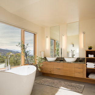 Example of a trendy master concrete floor and gray floor freestanding bathtub design in Denver with flat-panel cabinets, medium tone wood cabinets, beige walls, a vessel sink and multicolored countertops