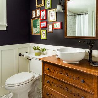 Diseño de cuarto de baño campestre, de tamaño medio, con sanitario de dos piezas, armarios tipo mueble, puertas de armario de madera oscura, paredes negras, lavabo sobreencimera, encimera de madera, suelo multicolor y encimeras marrones