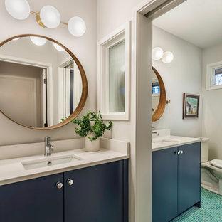 Foto de cuarto de baño infantil, retro, de tamaño medio, con armarios con paneles lisos, suelo con mosaicos de baldosas, suelo turquesa, puertas de armario azules, sanitario de dos piezas, paredes grises, lavabo bajoencimera y encimera de cuarcita