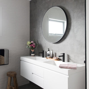 Photo of a mid-sized contemporary 3/4 bathroom in Canberra - Queanbeyan with white cabinets, a drop-in tub, a one-piece toilet, gray tile, porcelain tile, grey walls, porcelain floors, grey floor, flat-panel cabinets and an integrated sink.